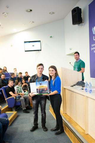 ASSIST Software representative handing the big prize, an Xbox One, to the winner